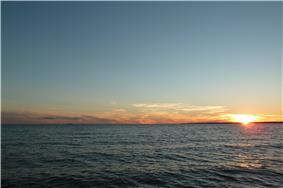 Sun setting over ocean waters
