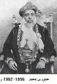 A black-and-white photograph of a man with a white beard wearing a turban, a dark jacket, a white shirt, and a belt and sitting on a chair