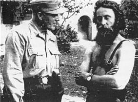 an SS officer in shirtsleeves and a mountain cap standing next to a bearded bare-chested man