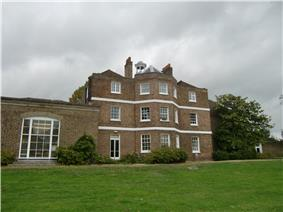 A three storey brown brick building with a cupola, and a single storey extension on the left, the foreground is a green lawn