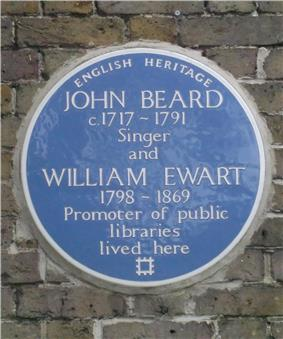 A Blue plaque on a brick wall with the words