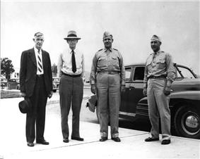 Four men stand in front of a car. The two on the left are wearing suits, the two on the right wear Army uniforms with garrison caps and ties tucked in.