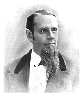 A middle-aged American gentleman of the immediate post-civil-war era. In this black-and-white portrait shot the subject looks to the viewer's right. His hair is short and sharply combed, and a beard is prominent on his chin. He wears a dark suit and white shirt.