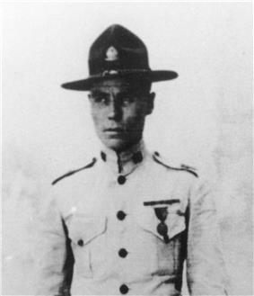 Top half of man in 1920s tropical U.S. Marine uniform with flat-brimmed campaign hat.