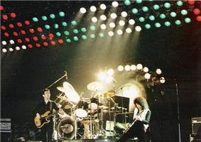 Three members of the group during a live performance in Hanover. From left to right, John Deacon (stood casually), Roger Taylor (playing, sat at drum kit), and Brian May (appears to be playing intensely). Behind Taylor is a tam-tam used at the end of Bohemian Rhapsody. Behind that is a large set of multicoloured lights raised above the stage.