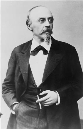 A balding man with a pointed beard, in formal dress clothes and holding a cigar in his left hand