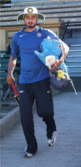 Man with black beard in a turban, wearing a white broad brimmed sunhat, is wearing navy tracksuit pants, blue T-shirt, and carrying light blue batting pads, a cricket bat and a helmet. Spectator seats can be seen in the background.