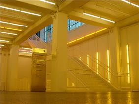 View of a below ground stairwell leading to the main floor in yellow light