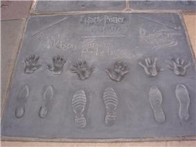An image of hand and feet impressions in a tile of concrete.