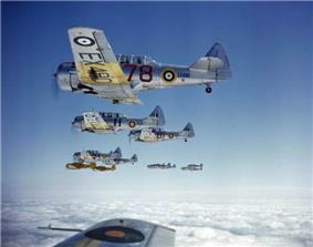 Silver fighter aircraft, marked with the British Royal Air Force's distinctive roundel, fly above the clouds in formation