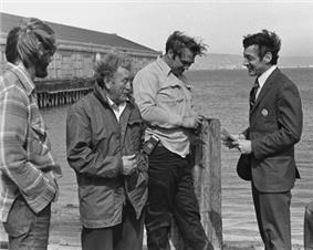 A black and white photograph of Milk in a suit with short hair speaking with three longshoremen standing by San Francisco Bay