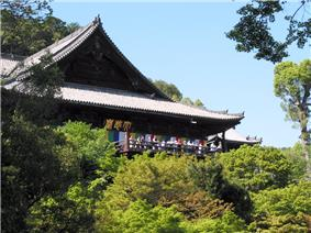 Wooden building with a large hip-and-gable roof built on a hillside. In front of the building there is a wooden railed platform.
