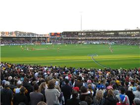 A small stand to the left and a two tier stand and scoreboard filled with people in the backdrop of an oval grass playing surface scattered with players. Spectators stand in the foreground.