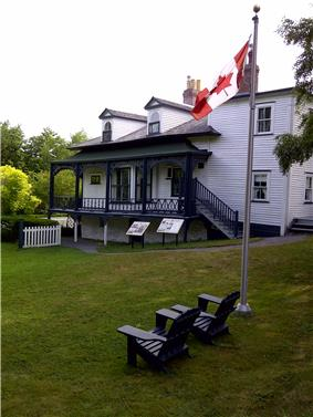 Two Muskoka chairs and a Canada flag overlooking Hawthorne Cottage