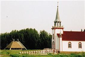 View of the side facade of Ste. Anne's Roman Catholic Church, with corner towers and projecting spire, and teepees