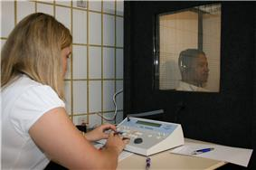 a female medical professional is seated in front of a special sound-proof booth with a glass window, controlling diagnostic test equipment. Inside the booth a middle aged man can be seen wearing headphones and is looking straight ahead of himself, not at the tester, and appears to be concentrating on hearing something