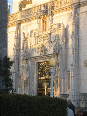 The grand entry door at the Hearst San Simeon Estate, with a great quantity of carved stonework, illuminated in the golden evening sun.