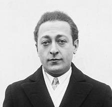head and shoulders shot of a man in overcoat, jacket and tie, looking at the camera