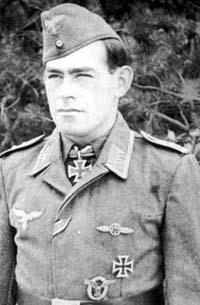 The head and upper body of a young man, shown in semi-profile. He wears a field cap and a military uniform with numerous military decorations including an Iron Cross displayed at the front of his shirt collar. His hair is dark and short, his nose is long and straight, and his facial expression is a determined and confident smile; his eyes gaze into the distance.