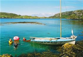 A small blue sailing dinghy lies in an aquamarine body of water next to a rocky shore underneath light blue skies. Three people are swimming off the stern of the boat next to a red buoy.