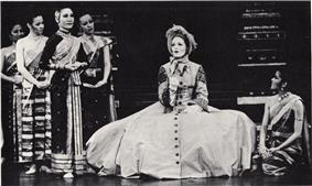 Black-and-white photo of a stage scene.  A Caucasian woman wearing a bonnet sits on a chair at center, with her huge Victorian hoop skirt spread out around her, singing.  Several women in elegant silky Asian clothing surround her.  One at right (Tuptim) kneels watching her, as the others stand in a clump at left.