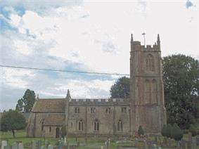 Stone building with arched windows. Prominent square tower to the right hand end. In the foreground are gravestones in grassy area.