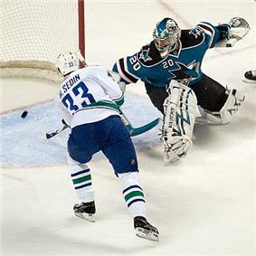 An ice hockey player wearing a white and blue jersey scores against a goaltender wearing a teal and black jersey with white pads.  The player has both hands on his stick outstretched to direct the puck in the net, while the goaltender is off balance looking back at the puck in his net.