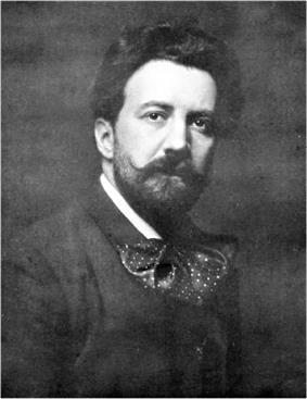 Head and shoulders picture of a young man with flowing medium length dark hair, a beard and moustache, and a huge floppy bow tie