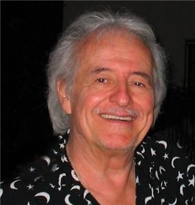A man with grey hair, wearing black and white shirt.