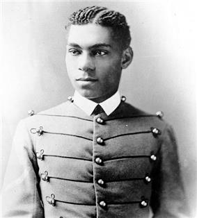 Cadet Henry O. Flipper in his West Point cadet uniform. It has three large round brass buttons left, middle and right showing five rows. The buttons are interconnected left to right and vice versa by decorative thread. He is wearing a starched white collar and no tie. He is a lighter colored African-American with plated corn rows of neatly done hair. He is facing the camera and looking to the left of the viewer.