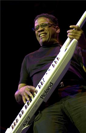 A man wearing glasses, with his eyes closed, playing a white keytar with black and white keys.