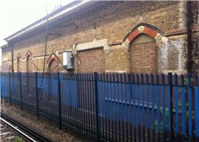 A brick building on the far side of a railway track, behind a blue metal fence. All of the doors and windows have been bricked up.