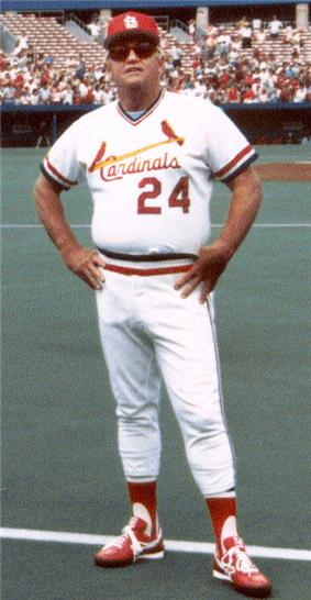 White man in his mid fifties wearing a white baseball jersey with red trim, a matching cap and sunglasses, standing on a baseball field