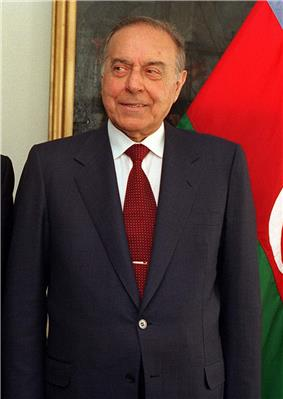 A man in a dark suit with a red tie standing in front of the Azerbaijani flag
