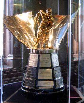 A trophy featuring a brass-coloured statuette of Richard atop a wood base with metal plates bearing the inscription of the trophy's winners