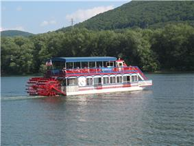 A red, white and blue paddlewheel boat with a sign