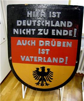 Black, red and gold West German sign reading