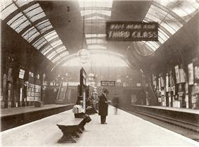A black-and-white photograph of a railway station platform under a barrel roof. Several figures are visible, one standing wearing a top hat, a sign reads