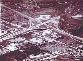 A four-leaf clover shaped highway junction, located in the midst of developing suburbs.