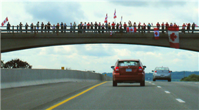 A bridge showcased against the sky, with the ground not visible. Lining the bridge are people, some holding Canadian flags.