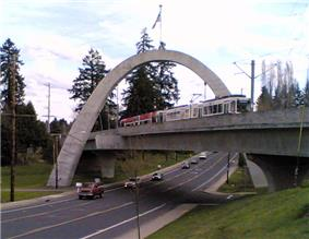 A MAX light rail train crossing the Main Street Bridge. The bridge is a tied concrete arch structure.