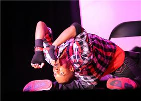 Male hip-hop dancer performing on stage inside a theater at Fort Belvoir army installation.