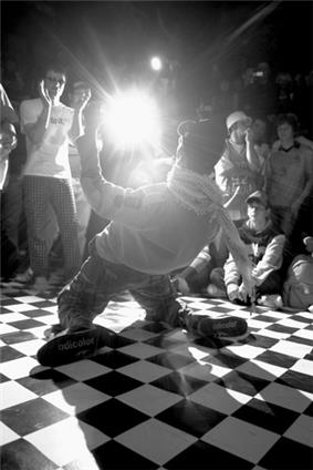 A close-up black and white photo of a male hip-hop dancer surrounded by a small crowd in a nightclub while performing on a checkerboard dance floor.