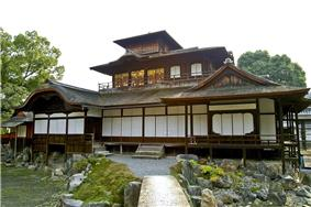 A three-storied wooden building with decreasing floor size with increasing level. The lowest level has white walls, the upper two have wooden walls. There is a veranda on the second level.