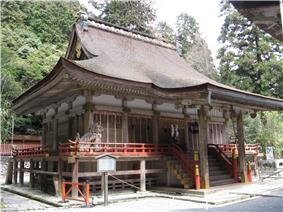 Three-quarter view of a proportionally tall wooden building with a veranda with red hand rail and a canopy covering the steps that lead to the central entrance. The roof appears to be a hip-and-gable roof.
