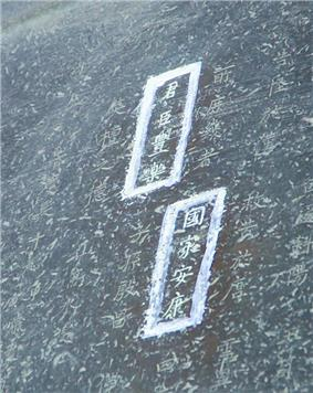 A close-up of Japanese script carved into a grey metallic surface; several characters are highlighted