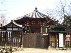 Small octagonal wooden building with white walls and red beams.