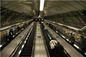 View up the inclined main escalator shaft with four escalators in a line carrying passengers up and down.