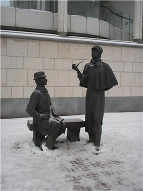 Sculpture of Holmes, standing holding his pipe, and Watson sitting on a bench