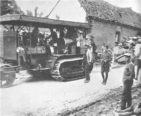 A Holt seventy-five tractor towing a field gun through a war-damaged village in Europe. The tractor is stacked high with supplies, and a number of uniformed soldiers are walking alongside.